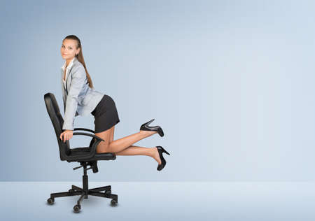 Businesswoman kneeling on office chair in empty room, looking at camera photo
