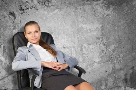 half turn: Businesswoman sitting on office chair with her arms clasped, in front of stone wall, looking at camera