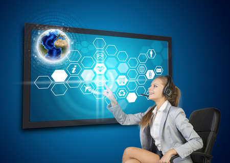 half turn: Businesswoman in headset pressing touch screen button on virtual interface with Globe and honeycomb shaped icons, on blue background.