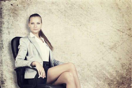 half turn: Businesswoman in office chair, looking at camera, over grunge scratchy background