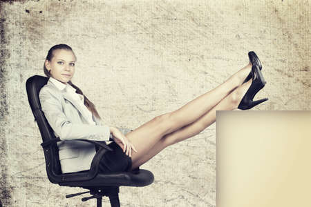 half turn: Businesswoman in office chair, looking at camera, with her feet up on anything, over grunge scratchy background Stock Photo