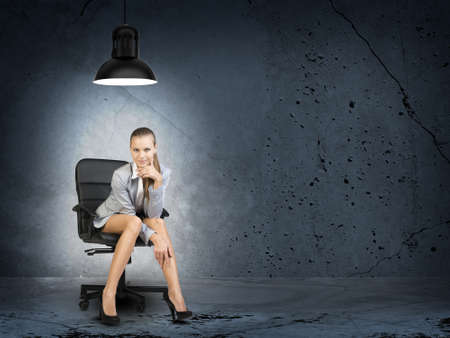 half turn: Businesswoman sitting on office chair in room in shell condition, lighted by lamp low above her head, looking at camera, smiling Stock Photo