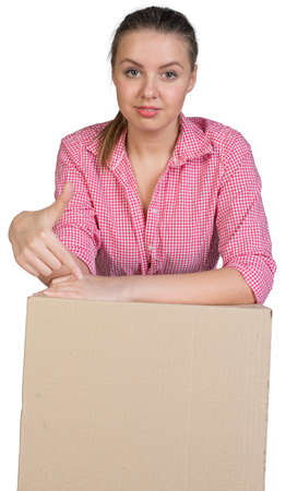 Sexy girl in shirt leaning on cardboard box and points finger at her, looking at camera. Isolated on white background photo