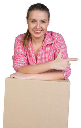 Sexy girl in shirt leaning on cardboard box and points finger in the direction, looking at camera. Isolated on white background Stock Photo