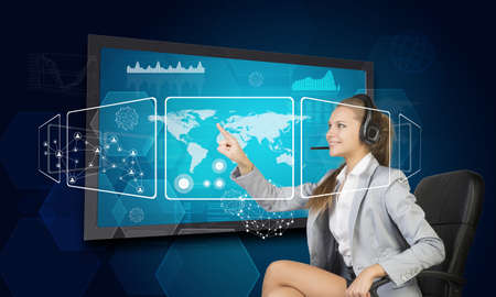 half turn: Businesswoman in headset using touch screen interface with world map, graphs and other elements, on blue