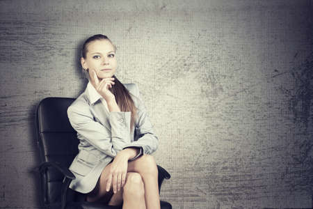 half turn: Businesswoman in office chair, looking at camera, over grunge scratchy  Stock Photo