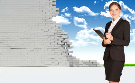 dilapidated wall: Businesswoman smiling and looking at camera. Dilapidated brick wall, green meadow and sky as backdrop. Business concept