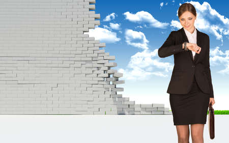 Businesswoman holding suitcase and looking at watch. Dilapidated brick wall, green meadow and sky as backdrop. Business concept photo