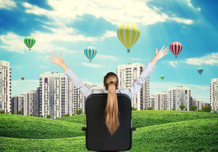 hands in the air: Businesswoman sitting on office chair with her hands outstretched. Green hills with buildings and sky as backdrop