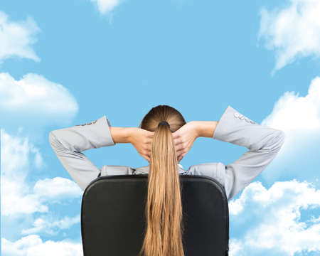 clasped: Businesswoman sitting on office chair with hands clasped behind her head. Sky with clouds as backdrop
