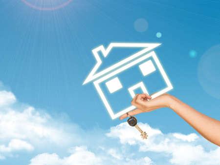 llave de sol: Mano femenina que sostiene icono y llaves casa. Cielo con nubes y sol en el fondo