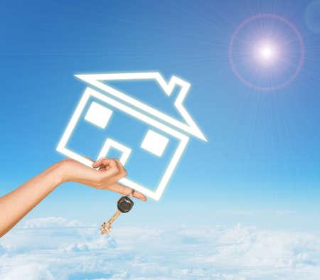 clave sol: Mano femenina que sostiene icono y llaves casa. Cielo con nubes y sol en el fondo