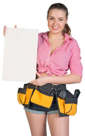 Woman in tool belt holding large white ceramic tile, looking at camera, smiling. Isolated on white background photo