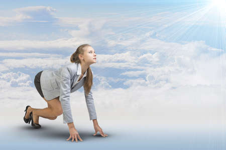 half turn: Businesswoman standing in running start pose, looking at light shining ahead. Sky and clouds as backdrop Stock Photo