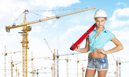 Woman in hard hat with large builders level on her shoulder, looking at camera. Sky, clouds and tower cranes as backdrop