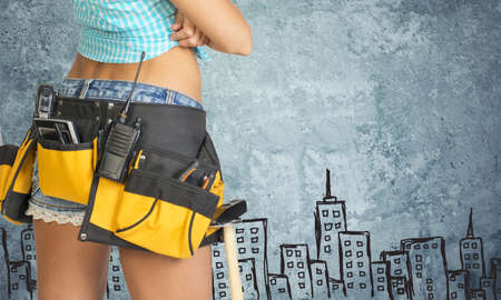tool belt: Close-up of woman in tool belt, with her hands crossed, against stone wall with sketch of city on it