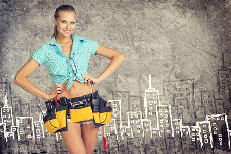 akimbo: Woman in tool belt standing akimbo against stone wall with sketch of city on it, looking at camera, smiling Stock Photo