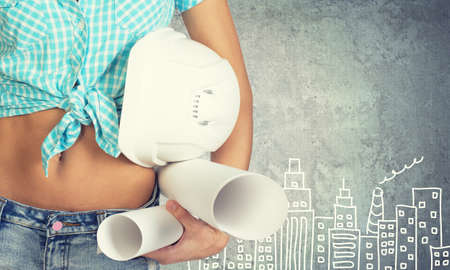 beer belly: Close-up of woman holding hard hat and drawing rolls, against stone wall with sketch of city on it Stock Photo