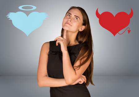devilish: Woman musing between angel and devil hearts. On gray background Stock Photo