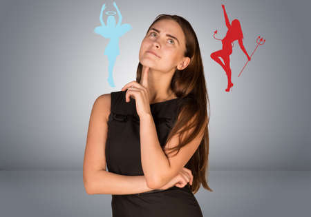 devilish: Woman musing between angelic and devilish figures. On gray background Stock Photo