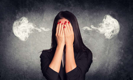 by ear: Close-up portrait of businesswoman hiding her face in her hands, with smoke from her ears. Raw concrete wall as backdrop Stock Photo