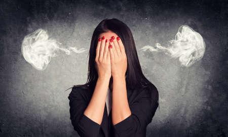 oido: Primer plano retrato de mujer de negocios que oculta su rostro en sus manos, con el humo de sus orejas. Muro de hormig�n en bruto como tel�n de fondo