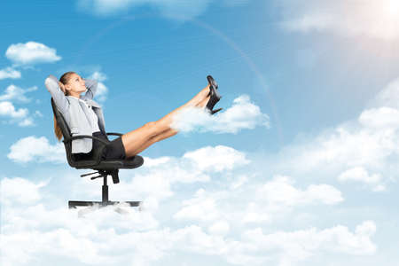 half turn: Businesswoman leaning back in office chair standing on cloud, with her feet up on smaller cloud, looking at light shining from above