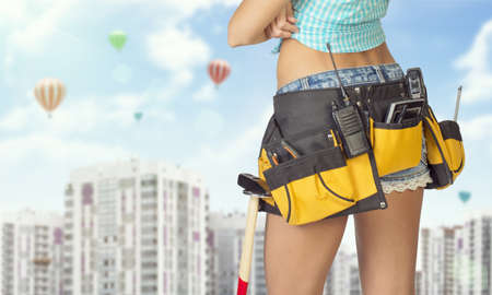 Woman in tool belt with different tools standing backwards, arms crossed. Cropped image. High-rise residential buildings and hot air balloons in background photo