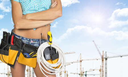 cropped image: Woman in tool belt with different tools stands his arms crossed. Cropped image. Tower cranes and blue sky in background