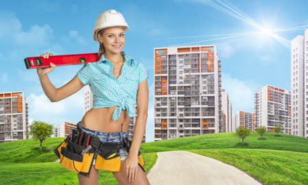 road shoulder: Woman in tool belt with different tools, white helmet, shirt and jeans holding building level on shoulder. Looking at camera, smiling. Green hills with road and buildings in background