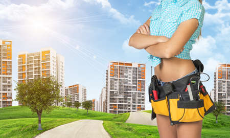 cropped image: Woman in tool belt with different tools stands his arms crossed. Cropped image. Green hills with road and high-rise residential buildings as backdrop