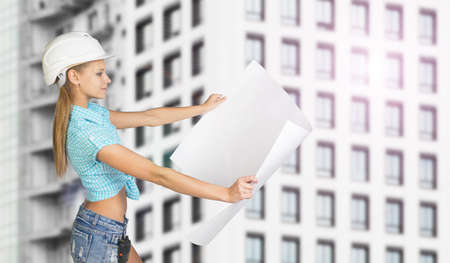 half turn: Woman in white helmet standing half turn and holding white paper sheet. Looks at paper, smiling. Building with windows as backdrop Stock Photo