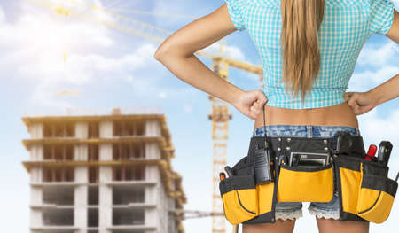 cropped image: Woman in tool belt with different tools standing backwards, akimbo. Cropped image. Building under construction in background