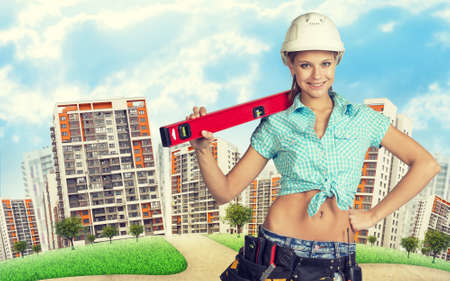 road shoulder: Woman in tool belt with different tools, white helmet, shirt and jeans holding building level on shoulder. Looking at camera, smiling. Green hill with road and buildings in background