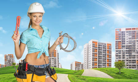adjustable spanner: Woman in white helmet holds adjustable spanner and two flexible hose. Looks at camera, smiling. Green hills with road and high-rise residential buildings as backdrop