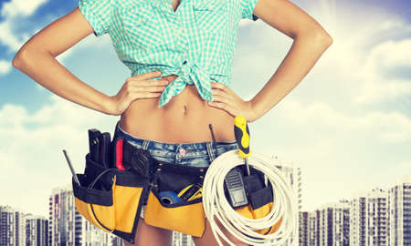 cat5: Woman in tool belt with different tools standing akimbo. Cropped image. High-rise residential buildings in background Stock Photo