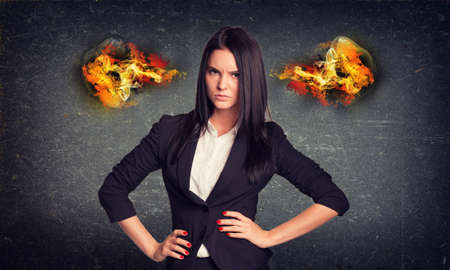 arms akimbo: Angry businesswoman standing with arms akimbo, fire from ears. Concrete wall in background Stock Photo