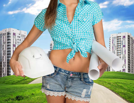 cropped image: Woman in shirt and short holding helmet and paper in hands. Cropped image. Green hills with road and buildings on background Stock Photo