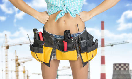 cat5: Woman in tool belt with different tools. Hands on hip. Cropped image. Tower cranes and chimneys on background