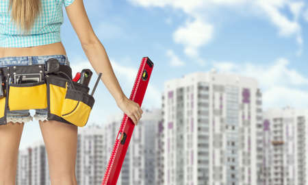 cropped image: Woman in tool belt with different tools holding red building level. Cropped image. Buildings and sky as backdrop