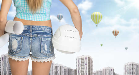 cropped image: Woman in shirt and short holding helmet and paper in hands. Back view. Cropped image. Buildings and sky with air balloons as backdrop