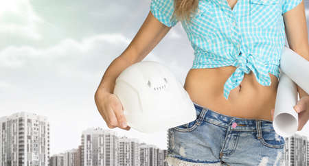 cropped image: Woman in shirt and short holding helmet and paper in hands. Cropped image. Buildings and sky as backdrop Stock Photo