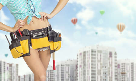 cropped image: Woman in tool belt with different tools. Hands on hip. Cropped image. Buildings and sky with air balloons on background