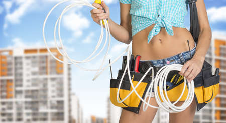 cropped image: Woman in tool belt with different tools holding electrical cable. Cropped image. Buildings and sky on background