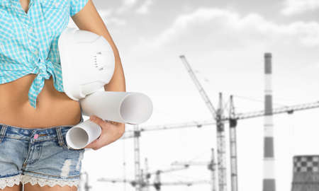 cropped image: Woman in shirt and short holding helmet and paper. Cropped image. Cranes and heat power stations on background