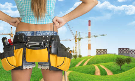 Woman in tool belt with different tools stands back. Hands on hip. Cropped image. Green hills and cranes with heat power stations on background photo