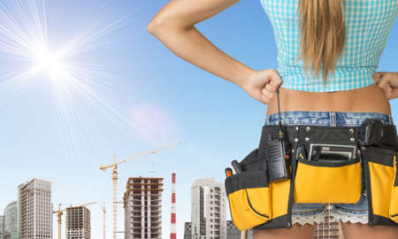 cropped image: Woman in tool belt with different tools stands back. Hands on hip. Cropped image. Building and sky as backdrop Stock Photo
