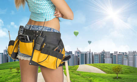 Woman in tool belt with different tools stands back. Cropped image. Green hills with road and buildings on background photo