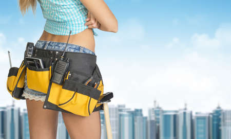 cropped image: Woman in tool belt with different tools stands back. Cropped image. Building and sky as backdrop