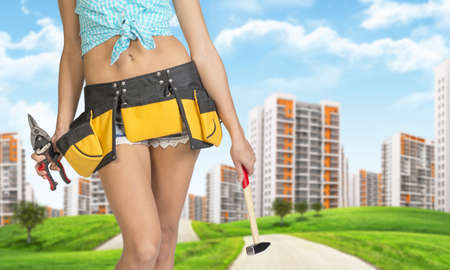 cropped image: Woman in tool belt holding hammer and pliers. Cropped image. Green hills with road and buildings on background Stock Photo